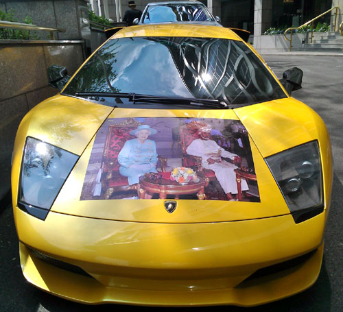 Picture of Queen Elizabeth II and the Sultan of Oman on the hood of a Yellow Lamborghini Gallardo