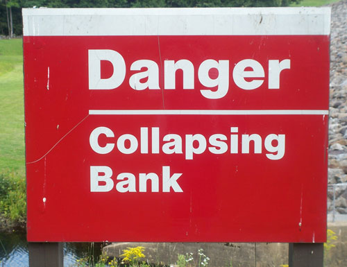 Sign At The Edge Of A Lake Stating Danger Collapsing Bank